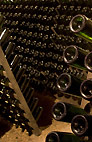 Sight of bottles in cellar - The ridding process done by hand on oak racks.